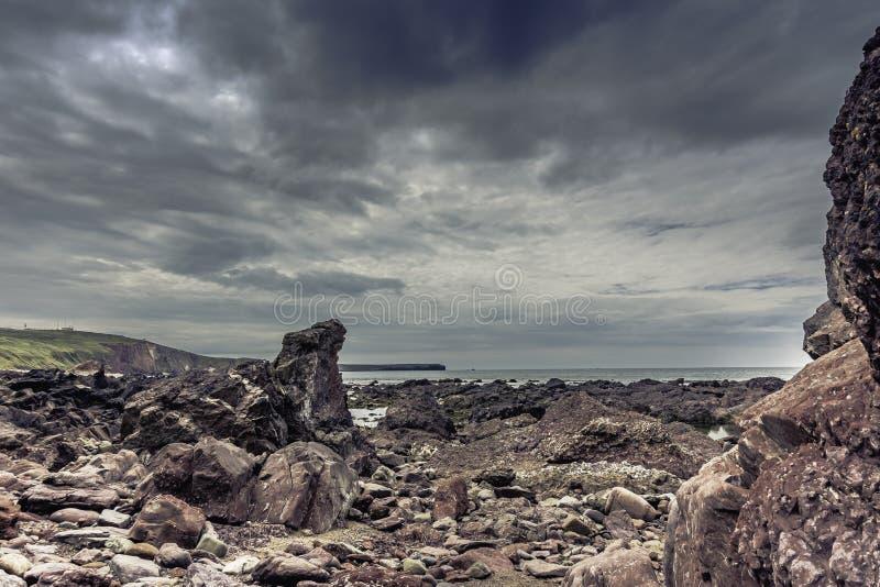 在南威尔斯,英国剧烈,岩石海岸线的喜怒无常的天空  免版税库存照片