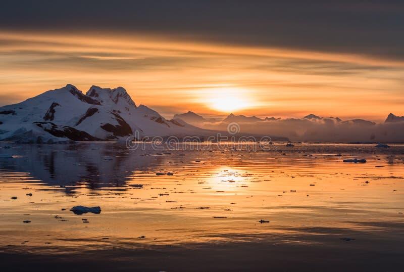 在南极盐水湖的日落有漂移的冰山和雪峰顶的在背景,勒梅尔海峡中 图库摄影