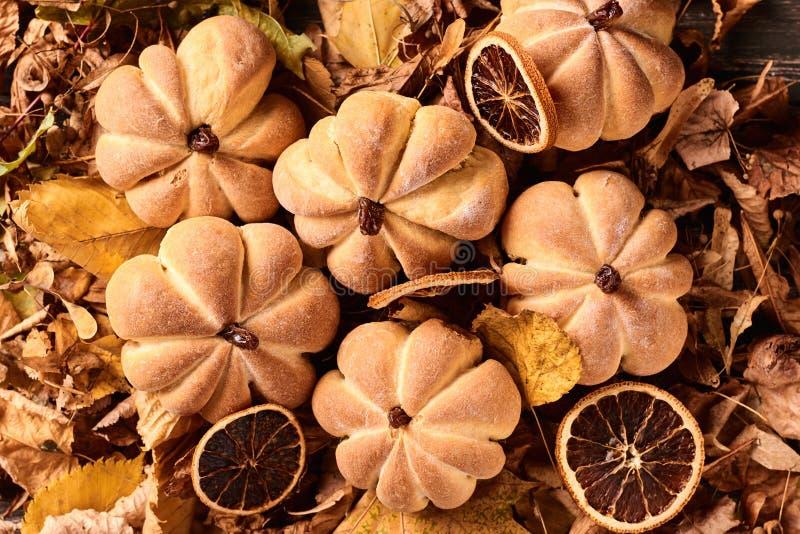 在南瓜形状的自创曲奇饼在秋叶的 在桌上的万圣节手工制造曲奇饼,关闭 免版税库存照片