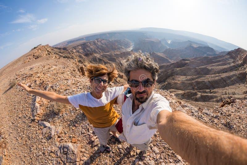 在南纳米比亚结合采取selfie在鱼河峡谷,风景旅行目的地 Fisheye视图从上面在背后照明 免版税库存图片