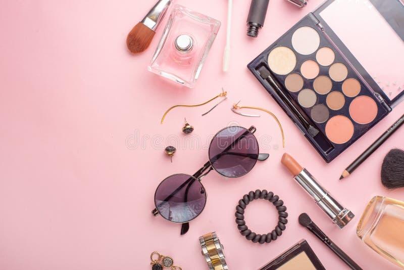 在博克的秀丽概念 专业女性构成辅助部件,手表,镯子,唇膏,粉末,在桃红色背景 ?? 免版税库存图片