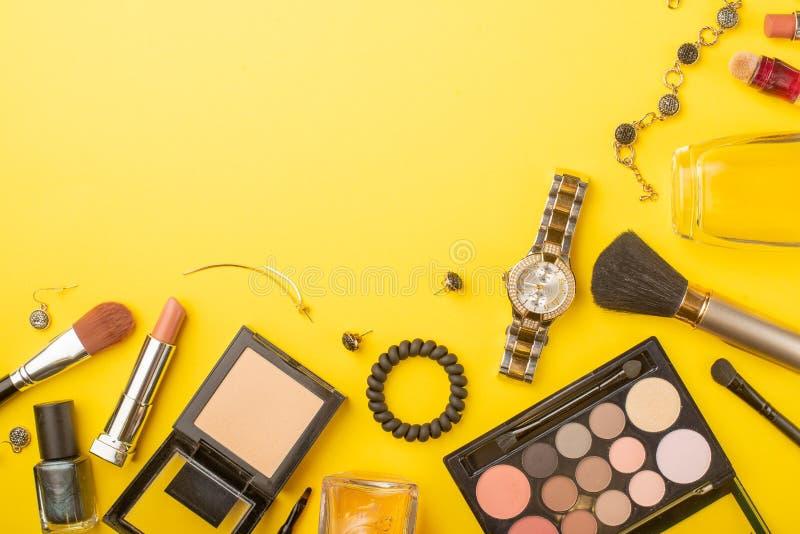 在博克的秀丽概念 专业女性构成辅助部件,手表,镯子,唇膏,粉末,在黄色背景 库存照片