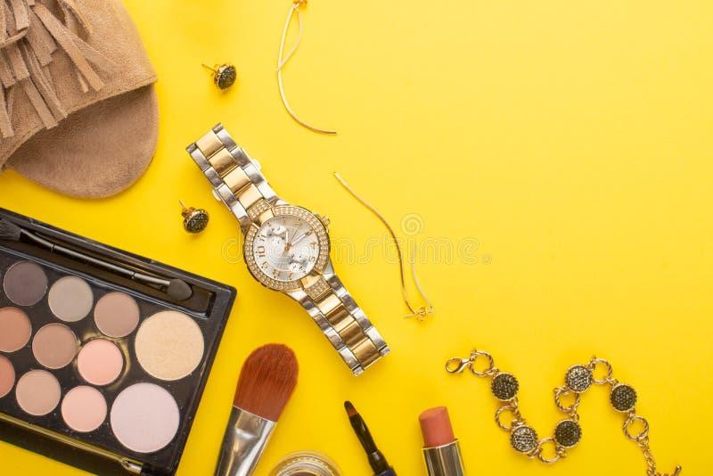 在博克的秀丽概念 专业女性构成辅助部件,手表,镯子,唇膏,粉末,在黄色背景 免版税库存照片