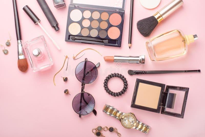 在博克的秀丽概念 专业女性构成辅助部件:手表,镯子,唇膏,粉末,在桃红色背景 ?? 免版税库存照片