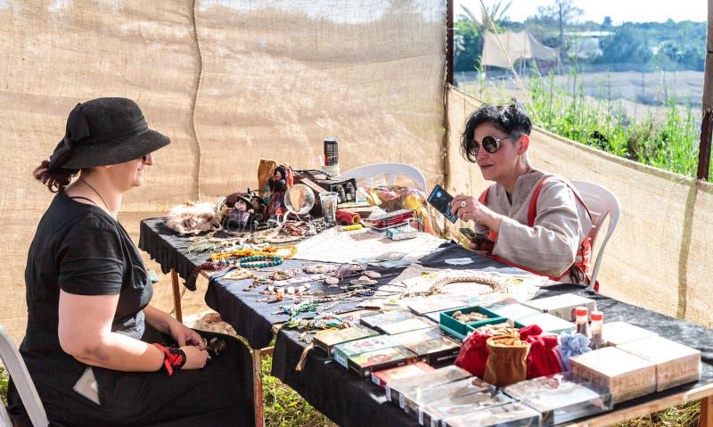 在占卜用的纸牌的算命者-骑士节日的参加者在戈伦公园回答访客问题在以色列 免版税库存照片