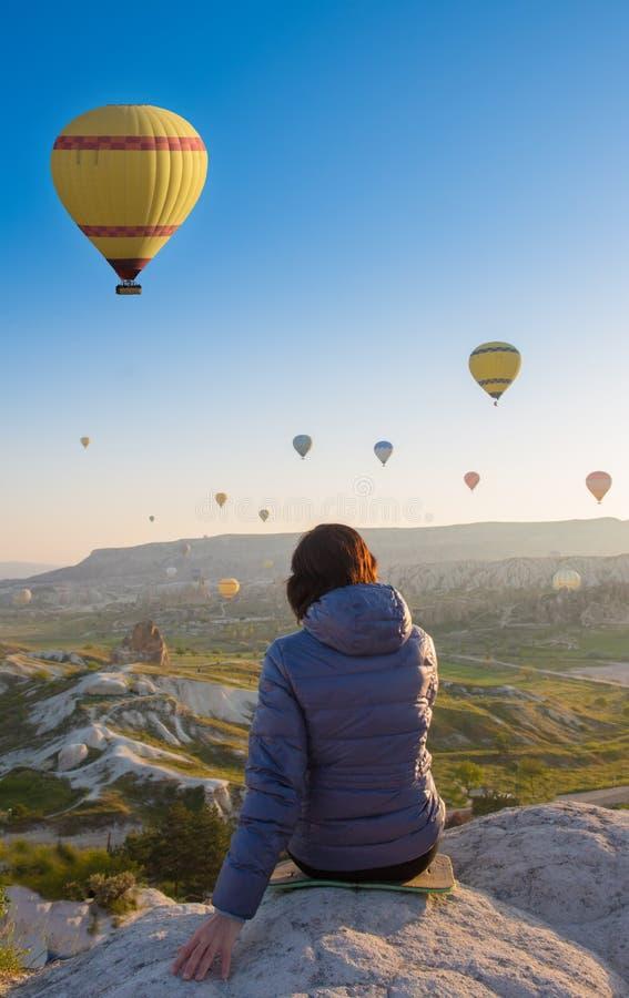 在卡帕多细亚小山顶部的妇女在清早日出,当气球飞行 浪漫卡帕多细亚场面,土耳其 库存图片