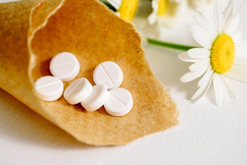 在卡拉服特klubke的白色片剂,绿色叶子药用植物,同种疗法药物 叶子菩提树,春黄菊flo花和果子  免版税库存照片