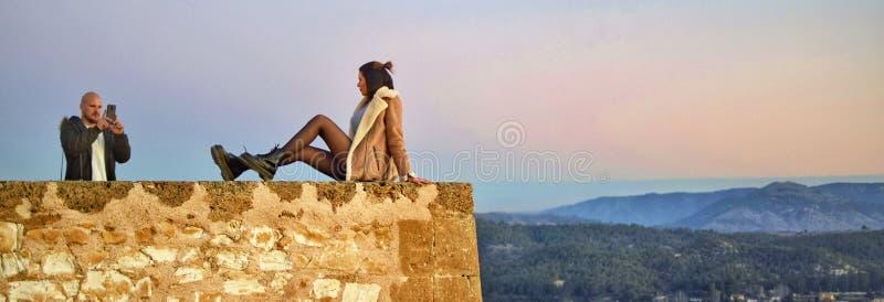 在卡拉瓦卡的城堡悬崖的旅游夫妇照相在西班牙 库存照片