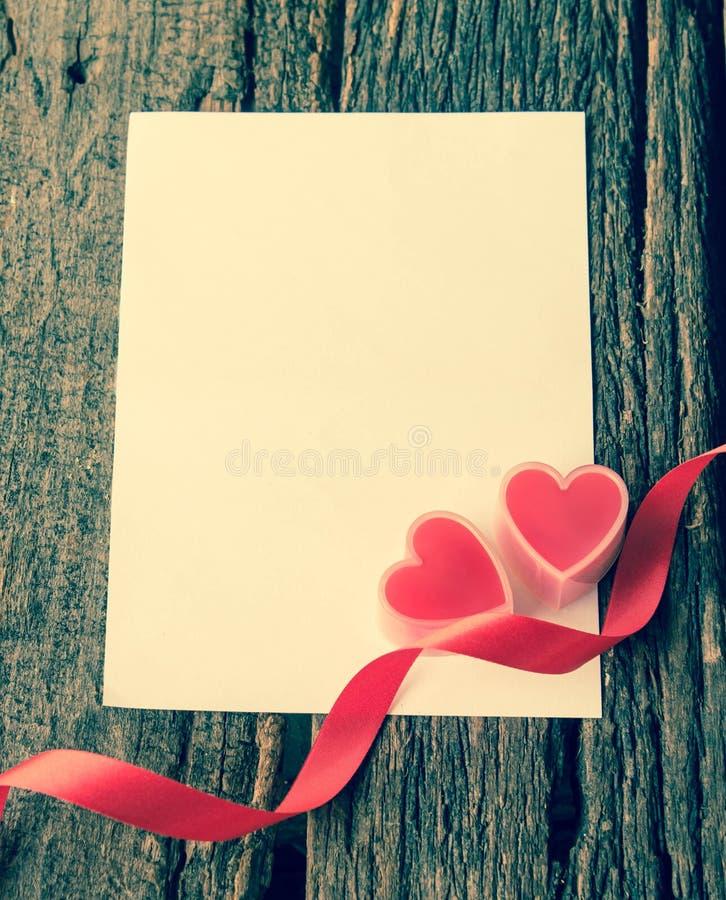 在卡片的红色心脏在纸的文本的 免版税库存照片