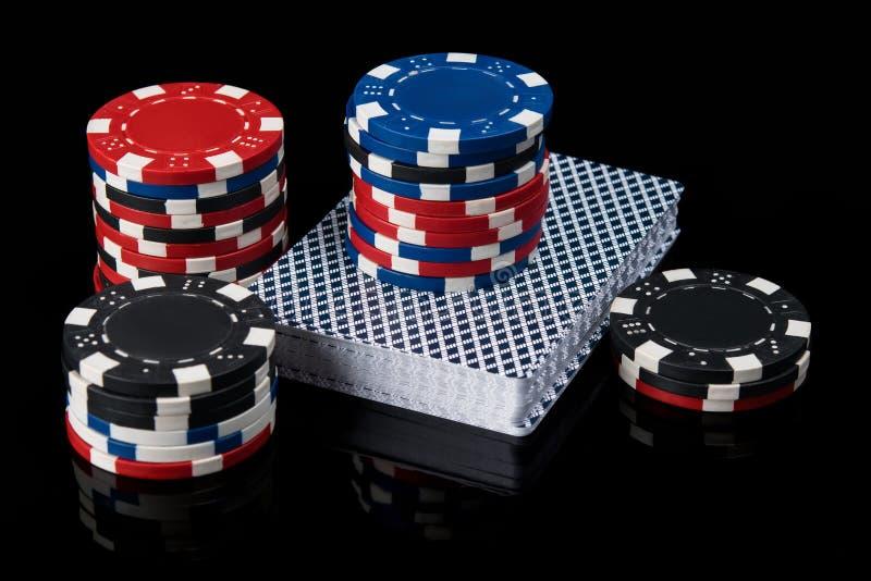 在卡片组的纸牌筹码打的扑克在与反射的黑背景 免版税库存图片
