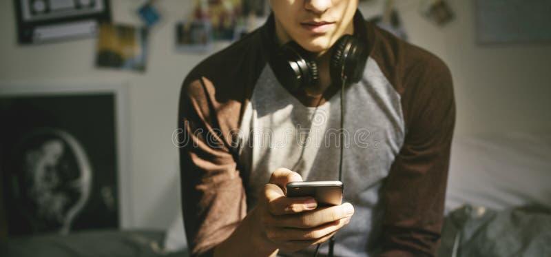 在卧室听到音乐的十几岁的男孩通过他的智能手机 库存图片