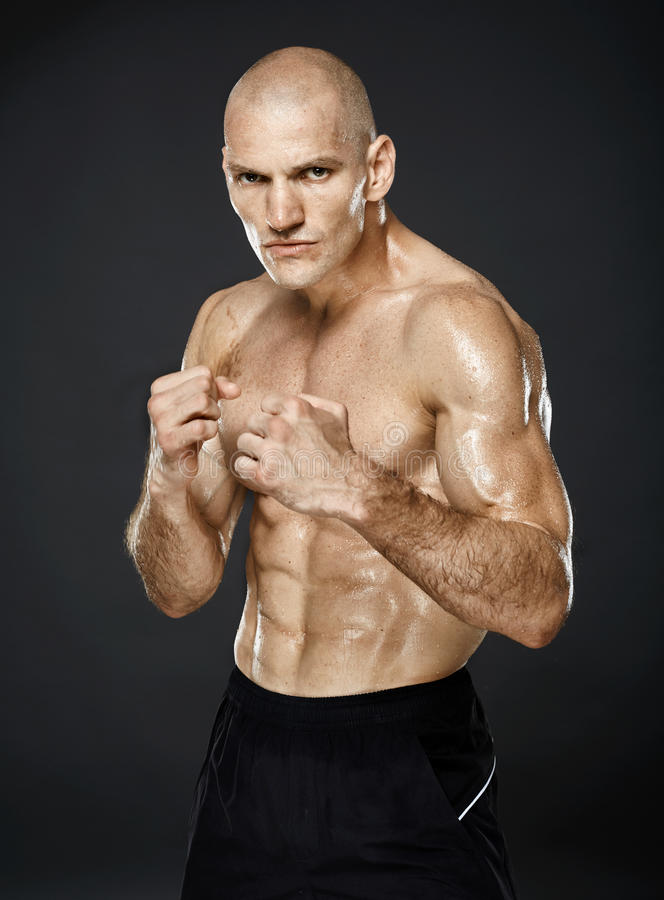 在卫兵姿态的Kickboxer在灰色背景 免版税库存照片