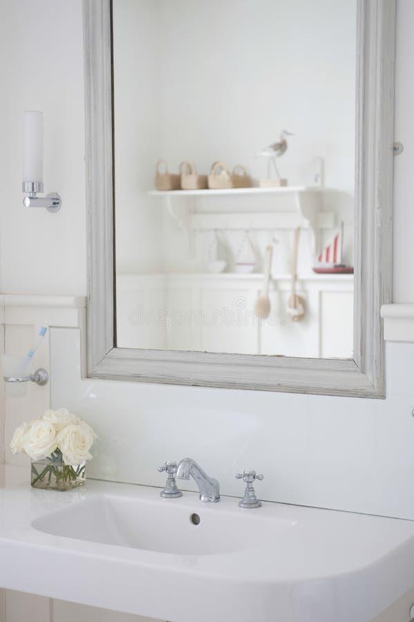 在卫生间水槽上的镜子 库存图片