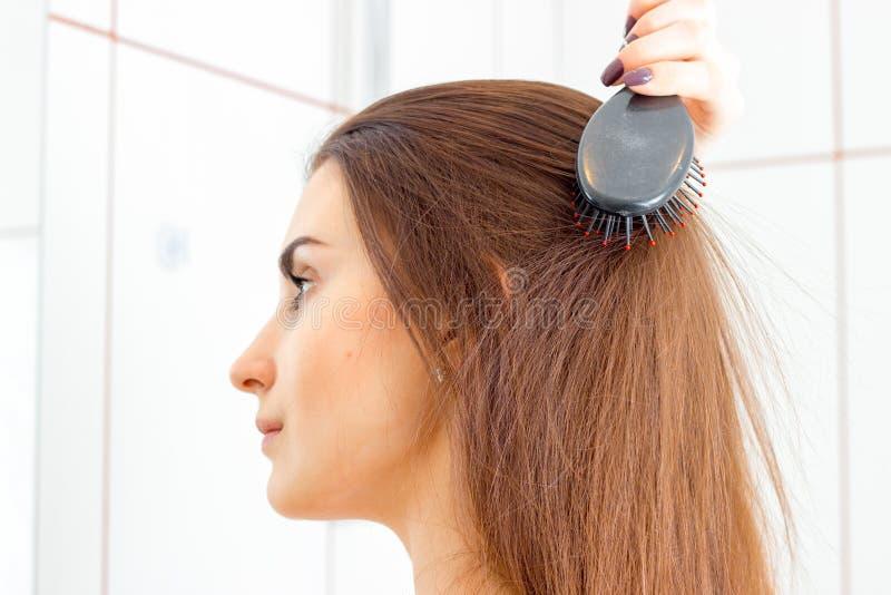 在卫生间里站立斜向一边并且梳她的头发一个女孩的画象 图库摄影
