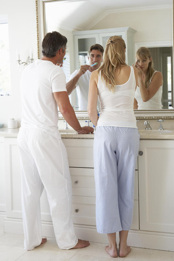 在卫生间镜子的夫妇掠过的牙 免版税库存图片