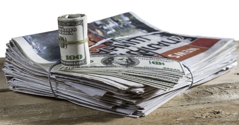 在印刷品报纸的金钱 免版税库存照片