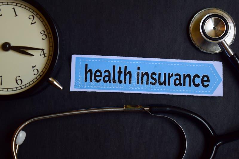 在印刷品纸的健康保险与医疗保健概念启发 闹钟,黑听诊器 免版税图库摄影