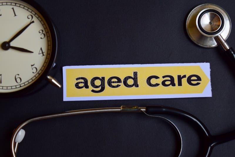 在印刷品纸的年迈的关心与医疗保健概念启发 闹钟,黑听诊器 免版税库存图片