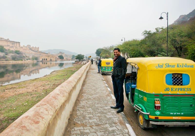 在印地安moto人力车附近的英俊的印地安司机立场 库存图片