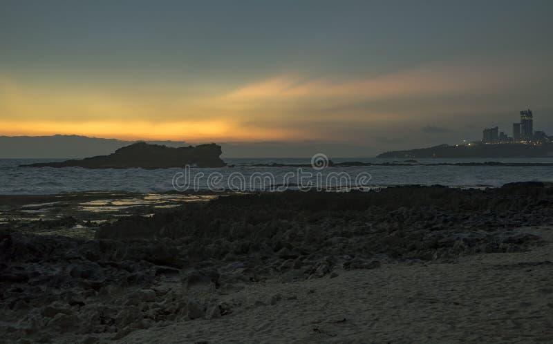 在印尼爪哇巴尤的海滩上,看到大型水泥厂或类似的生意,日落时光很美 免版税库存图片