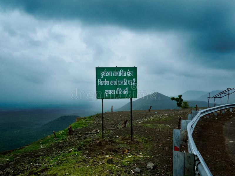 在印度的倾斜的山路的警报信号 库存照片