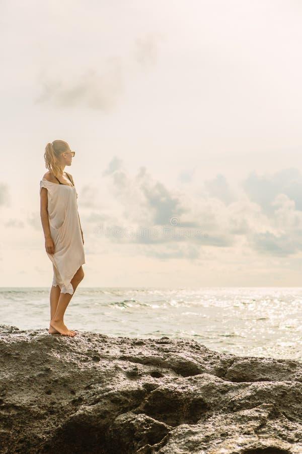 在危险岩石附近的俏丽的妇女在海洋岸 库存照片