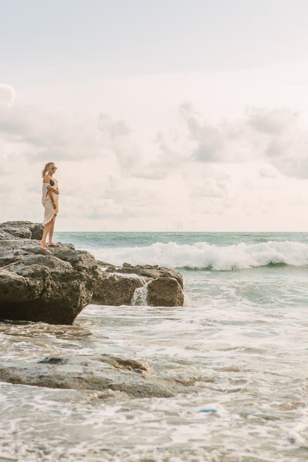 在危险岩石附近的俏丽的妇女在海洋岸 免版税库存照片