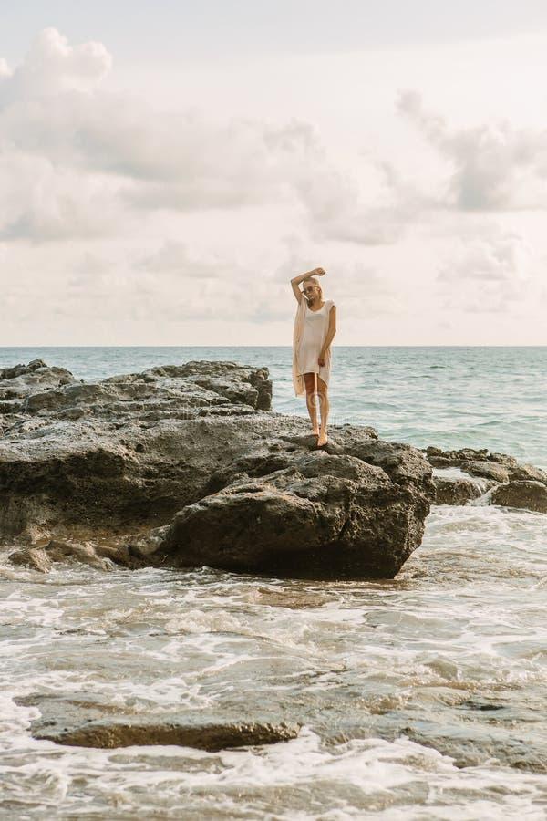 在危险岩石附近的俏丽的妇女在海洋岸 免版税图库摄影