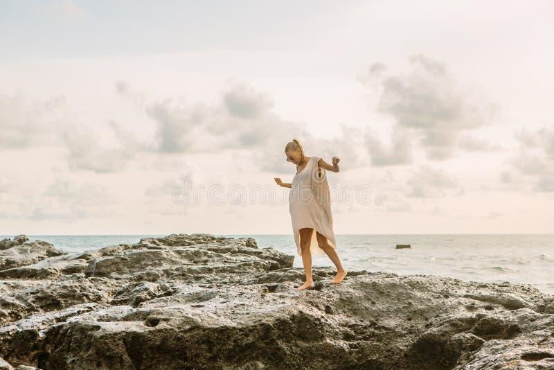 在危险岩石附近的俏丽的妇女在海洋岸 免版税库存图片