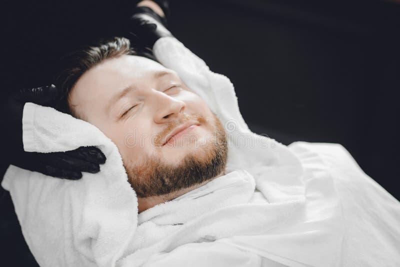 在危险皇家刮脸前面的脸部按摩 刮的胡子和的髭,与热的毛巾的蒸汽 概念理发店 免版税图库摄影