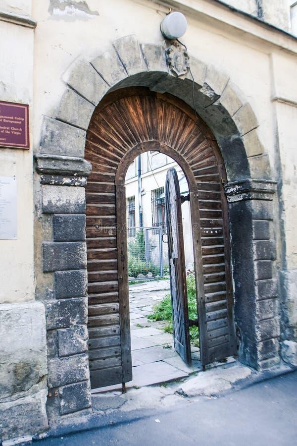 在卵形石曲拱的古老的木门开放入围场 免版税图库摄影