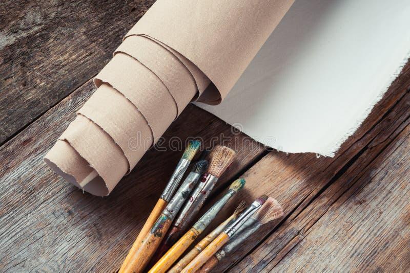 在卷和油漆刷的艺术家帆布在桌上 库存照片