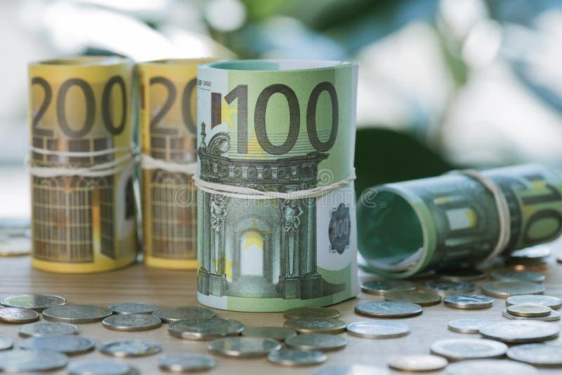 在卷的欧洲在桌上的钞票与橡皮筋儿和硬币 免版税库存图片
