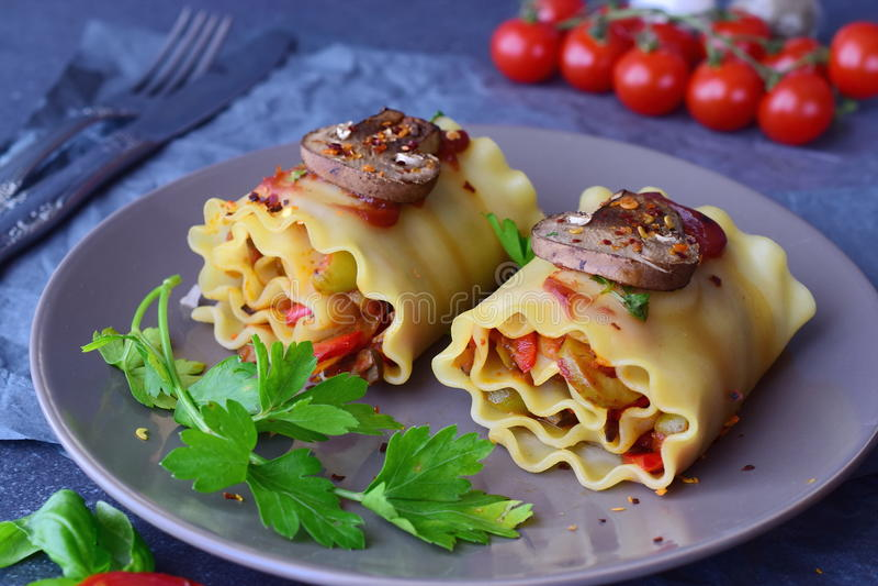 在卷的立即可食的素食烤宽面条用蘑菇,辣椒粉,橄榄,在一块棕色陶瓷板材的西红柿酱 健康 库存图片