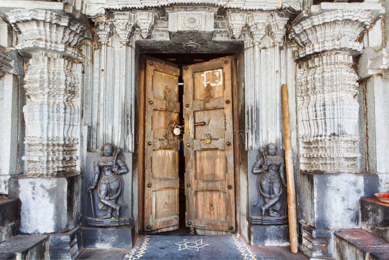在历史印度寺庙的木门有石墙、collumns、雕刻和雕塑的,印度 图库摄影