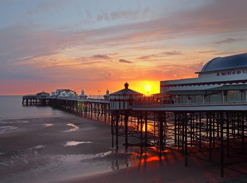 在历史的北部码头的太阳设置在有在海滩和五颜六色的暮色天空反射的发光的光的布莱克浦 免版税库存图片