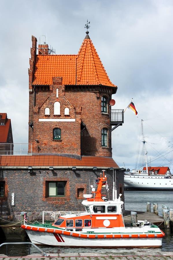 在历史砖瓦房前面的救助艇在施特拉尔松德 库存照片