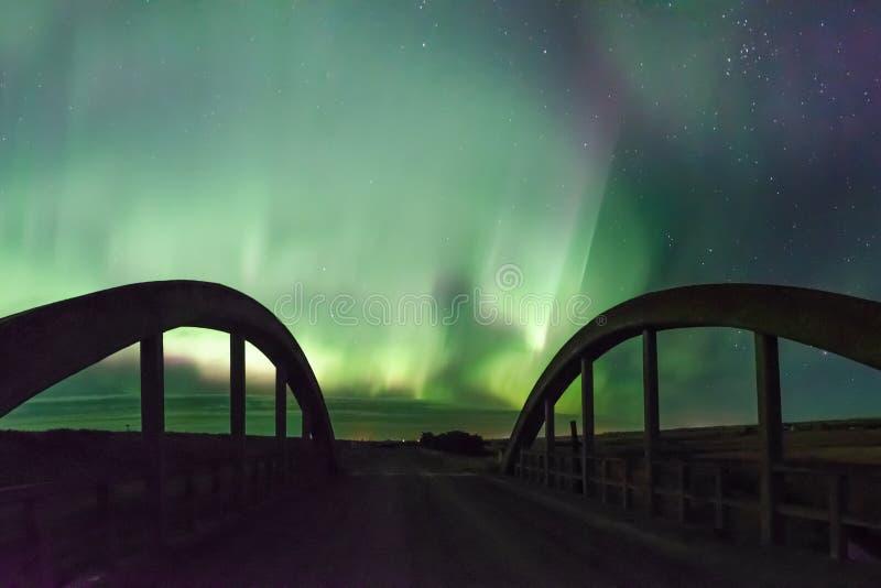 在历史Rush湖小河桥梁的极光Borealis北极光在萨斯喀彻温省,加拿大 免版税库存图片