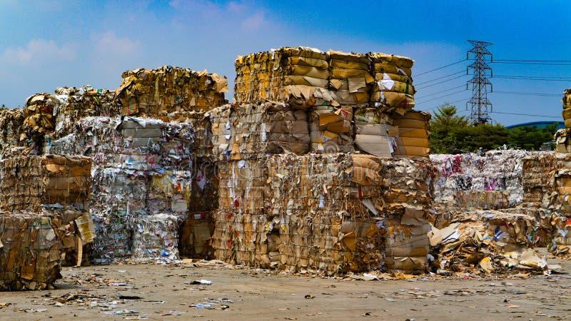 在压入水力打包的垃圾新闻机器以后回收产业纸板垃圾和纸废物对密集的正方形 免版税图库摄影