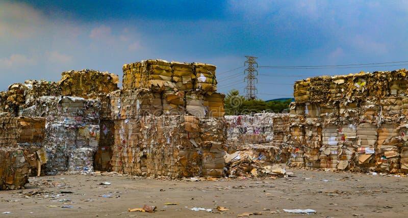 在压入水力打包的垃圾新闻机器以后回收产业纸板垃圾和纸废物对密集的正方形 免版税库存照片