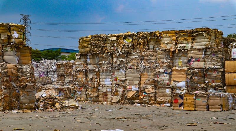 在压入水力打包的垃圾新闻机器以后回收产业纸板垃圾和纸废物对密集的正方形 免版税库存图片