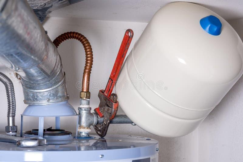 在压缩坦克的水管工板钳在一个热水加热器 免版税库存图片