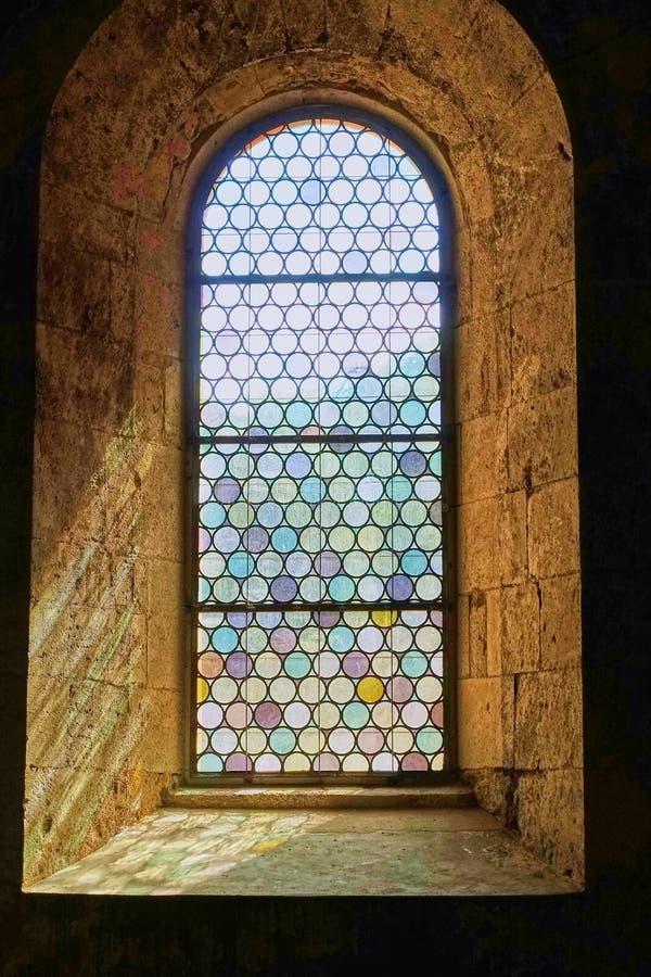在厚实的石墙设置的俏丽的行间空格特别大的污迹玻璃窗 免版税库存图片