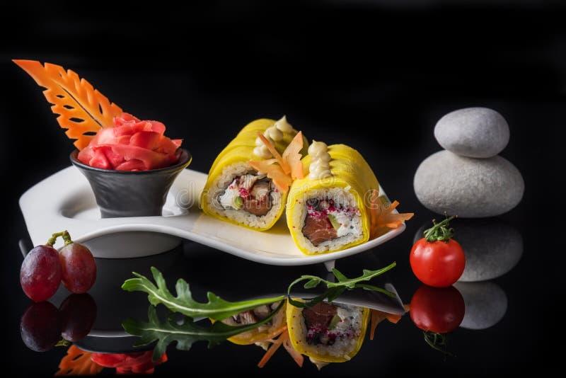 在原始的板材的寿司卷在黑色 艺术照片 免版税库存照片