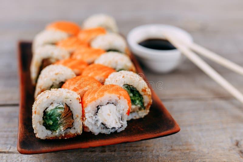 在原始的黏土板材的日本maki寿司卷 免版税图库摄影