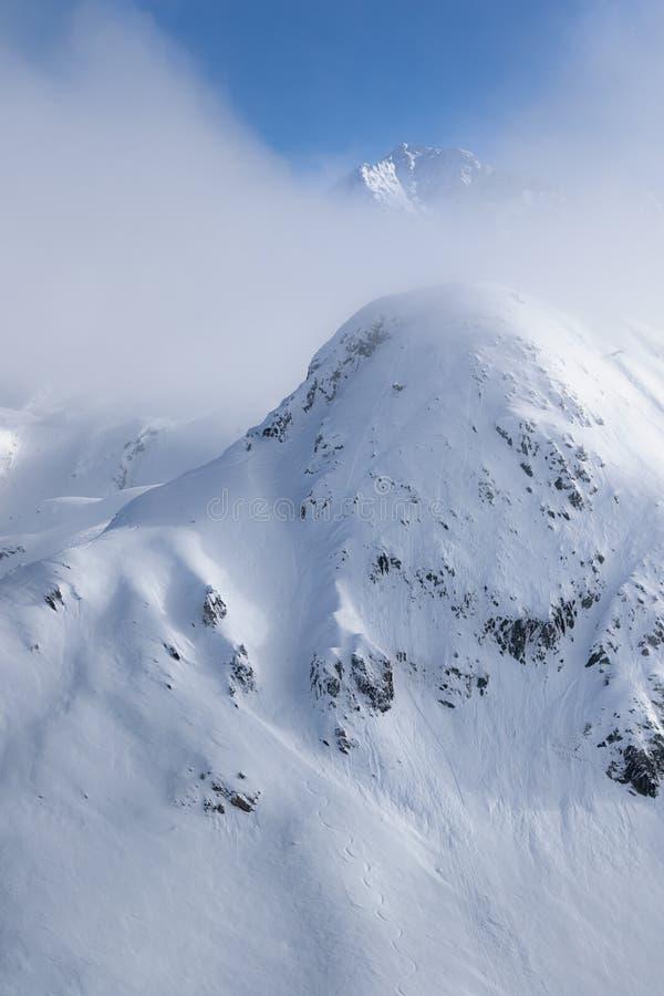 在原始高山风景的暗藏的山峰 镇静和平静的冬天风景在法国萨瓦山,滑雪场La皮拉涅 免版税库存图片