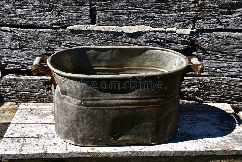 在原木小屋前面的老铜锅炉 库存照片