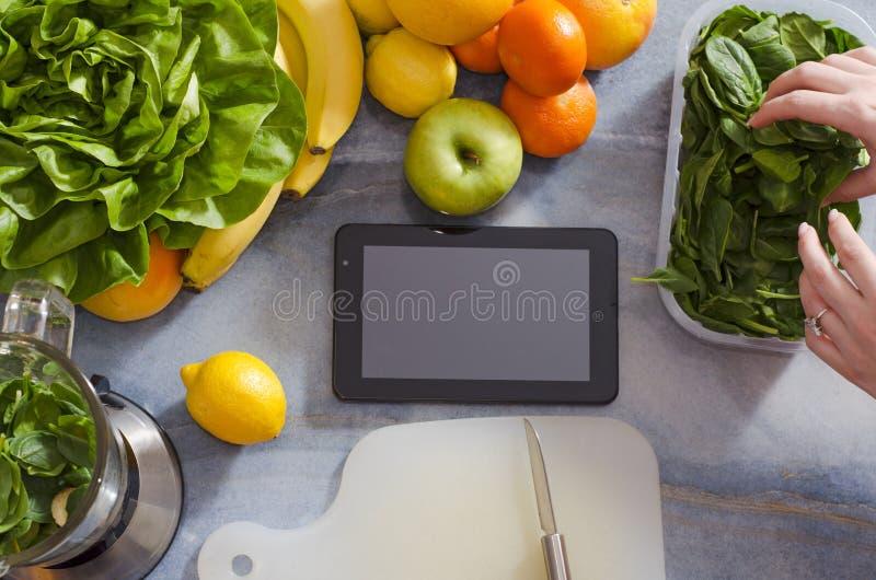 在厨台、拷贝空间、水果和蔬菜的片剂在它旁边 库存图片