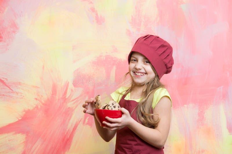 在厨师帽子、围裙举行曲奇饼或者饼干的厨师孩子 库存照片