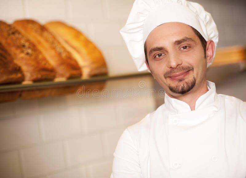 在厨师的服装穿戴的面包店所有者 图库摄影